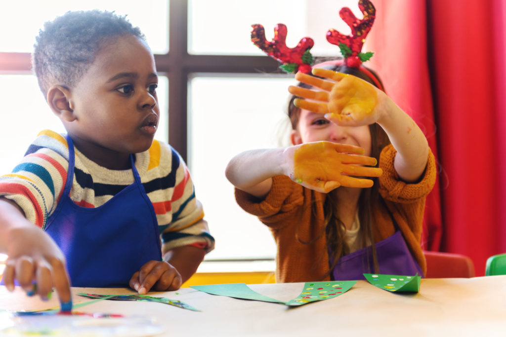 young kids doing homemade decorations for Christmas at a table with girl wearing antlers