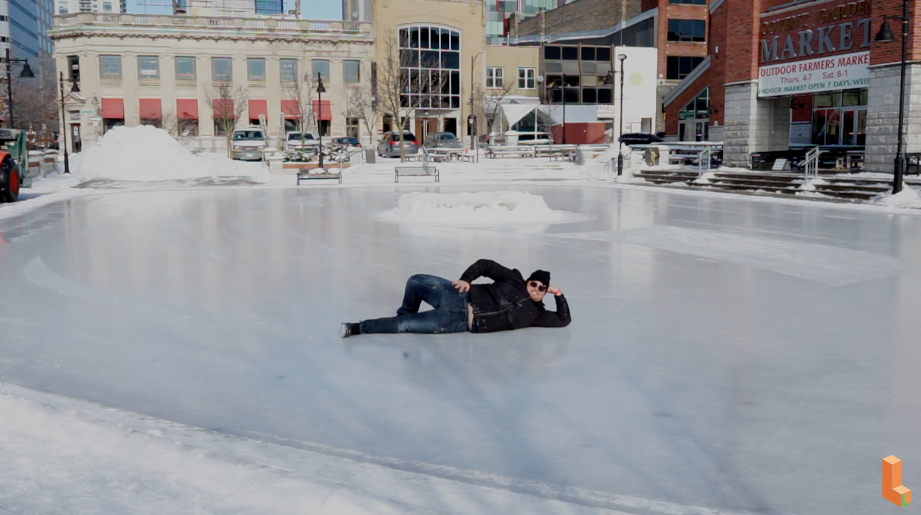 man posing lying on skating rink alone in front of some buildings